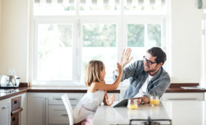 girl using a digital tablet with her father at home