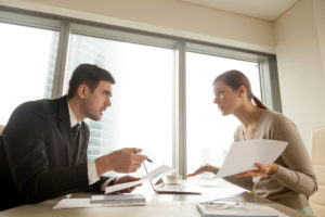 Colleagues arguing at workplace, disagree about document, error in contract