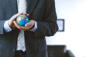 Buisnessman holds a small globe in his hands